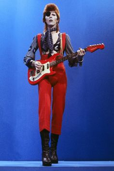 """An eye-patched Bowie performs """"Rebel Rebel"""" on the TV show TopPop on the 7th of February 1974 with a knotted silk scarf and crimson dungarees to boot. #refinery29 http://www.refinery29.uk/2016/01/100928/david-bowie-death-2016#slide-11"""