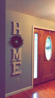 Large wooden letters. Home decor Farmhouse style decorating. HOME. Decorating with wreaths. Foyer farmhouse decorating. Front entrance decorating. Mindful gray Sherwin Williams painted walls. Front door. Hobby Lobby decor. White distressed letters.