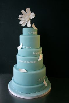 A single flower adorns a cake decorated with petals and declarations of love in French, by Sugarplum Cake Shop.