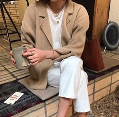 Camel cardigan coat, white T shirt and trousers.