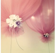 Tulle wrapped over balloons tied with ribbon and flowers. Adorable for baby shower!