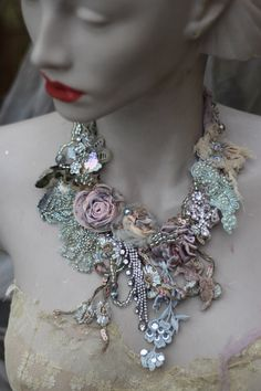 Experimental necklace of the small series with antique laces& hand embroidery.This shabby chic detailed neckpiece is made of wide array vintage and antique textiles. Textured and embroidered vintage silks, sculpted satin flowers , trims and laces were intuitively hand sewn and embroidered into intricate composition, encrusted with hand beading, crystals, pearls and finds. Necklace has soft lining for more comfort, closes with soft tulle ribbons at back. Width varies from 4 to 6-8 cm at…