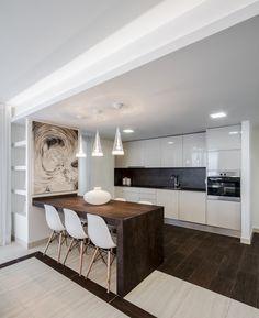 Cocina abierta al salón con mesa adosada a la pared