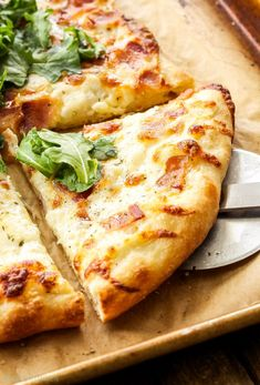 White Pizza with Bacon and Arugula   Topped with a parmesan cream sauce, smoked mozzarella, bacon and a fresh arugula salad, it's sure to become your favorite white pizza!