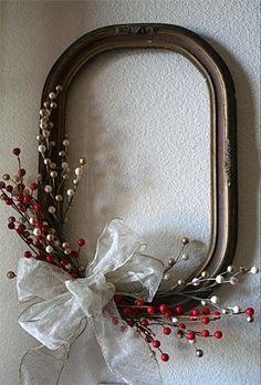 antique picture frame decorated similar to a wreath for wall decoration at Christmas. Could hang family initial inside & use as door wreath too
