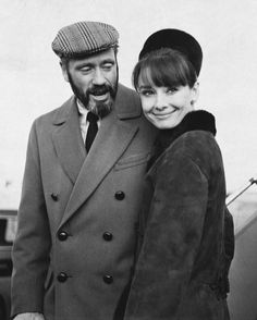 """Mel Ferrer with his wife Audrey Hepburn photographed arriving at theHeathrow Airportin London (England) from Zurich (Switzerland), for the premiere of her latest film """"My Fair Lady"""", at theWarner Theatre. London (England), January 19, 1965. -Audrey was wearing creations ofHubert de Givenchy(coat of suede with black fur, created especially for her and pillbox hat lined with black fur, of his collection for the Autumn/Winter 1964/65)."""