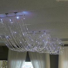 Our Crystal LED ceiling curtain is 15 feet long, 20 inches wide and has 30 strands of beads, five of the strands contain LED lights on thin, silver wire. One end of the crystal acrylic bead drape h. Ceiling Draping, Ceiling Curtains, Led Ceiling, Luz Led Diy, Denim And Diamonds, Diy Chandelier, Chandelier Centerpiece, Led Licht, String Lights Outdoor