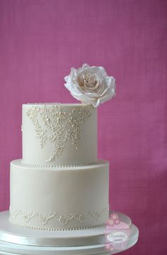 "Ivory wedding cake with hand piped decoration inspired by the bride's Blue by Enzoani ""Iva"" wedding dress, topped with a sugar rose."