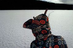 Figure wearing hooded garment made from a blanket, on a frozen lake.   Welsh woollen textile woven by Melyn Tregwynt, Wales.  http://www.melintregwynt.co.uk/designs/knot-garden/804014