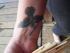 In just black and gray, this flying bird tattoo is a bit more bold and yet still delicate on the wrist.