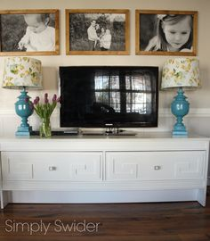 Mid-century modern Greek key TV console with architectural lamps paint teal and framed engineering prints.