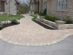 A mix of earthtones in the manufactured brick walkway match the brick in the house as well as the pavement in the driveway. Picture compliments of www.ogslandscape.ca