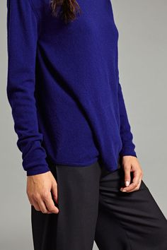 Celia Cashmere Pullover In Bright Navy.  This cashmere pullover features asymmetrical draping at the front, giving it a subtly distinctive silhouette. It is long sleeved with a slightly raised neckline.