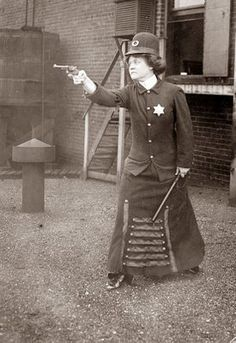This picture is from the 1920's and shows a police woman with a Billy Club and packing a pistol.