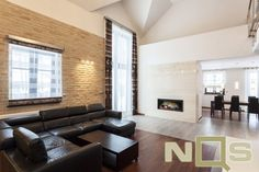 Stylish living room design with a fireplace made from white synthetic granite. A large sectional leather couch and a light brown brick wall made a big impression on visitors. Painted Brick Walls, Brick Accent Walls, Red Brick Walls, Exposed Brick Walls, Faux Brick Panels, Brick Paneling, Brick Fireplace Wall, Fireplace Design, Loft Stil