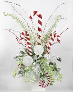 """Capture the whimsy and elegance of Christmas with this Candy Cane Centerpiece. Filled with an abundance of special features including: - Candy canes, including one 17""""H and four 12""""H, and three more g"""