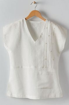 Sewing Blusas Renu Top - Soft white - Made by Nirmaan Asymmetrical pleats with embroidery accents highlight this new take on a tee. V-neck linen/cotton blend with hand embroidery. Cap sleeves and side slits. Sewing Clothes Women, Clothes For Women, Misses Clothing, Linen Blouse, Petite Outfits, Linen Dresses, Latest Fashion For Women, Womens Fashion, Refashion
