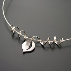 "Pendant | Aileen Lampman.  ""Leaf and Tendril"".  Sterling silver, hanging from a sterling cable wire."