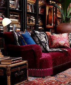 Rich colours and bohemian flair in this room with a burgundy sofa against dark wood bookcases with a large planter raised off the floor