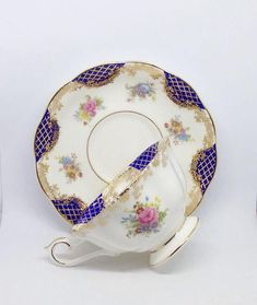 Royal Albert Empress Series, Isabella tea cup and saucer, with navy colored elements latticed with gold and garlands. In excellent condition.