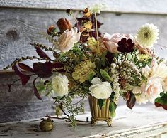Tin Can Studios. Wild and loose, ranunculus, champagne roses, plum leaves, dahlias, persimmons in a brass footed vase.