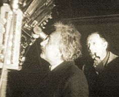 Einstein with Edwin Hubble, in 1931, at the Mount Wilson Observatory in California, looking through the lens of the 100-inch telescope through which Hubble discovered the expansion of the universe in 1929. - Courtesy of the Archives, Calif Inst of Technology.