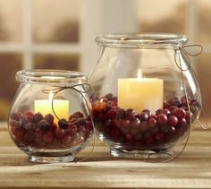 Vase filled with cranberries, a short white candle, and a bow around the top