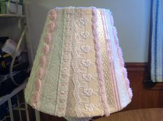 Shabby chic lampshade.     Glue lace trim and ribbon onto a white or cream colored lampshade.