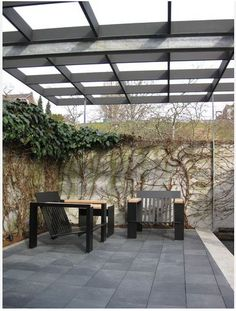 Metal square pergola with stone squares mirror one another.