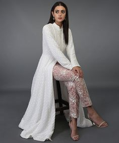 Valentine musing over this Ivory hand embroidered chikankari kalidaar suit. It is teamed with a net floral embroidered cigar pant/skirt enhanced with a nude blush inner taffeta lining. Grab the look for yourself or your loved ones! Salwar Designs, Kurta Designs Women, Kurti Designs Party Wear, Indian Attire, Indian Wear, Indian Suits, Pakistani Dresses, Indian Dresses, Lehenga