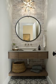"""I like the simple floating vanity and the floating shelf beneath. The plain round mirror is a perfect foil to all the rectangular elements. The brick is a great backdrop, too. """"While it may look like an exposed wall of a loft or reclaimed warehouse, it's in fact made of a brick veneer product that the designer over-grouted using a German smear technique"""" Roomspiration, Half Baths, Powder Room, Home Renovation, Backsplash, Bathroom Ideas, Bathrooms, Toilets, Trough Sink"""