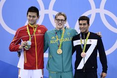 Australia's Mack Horton (C) poses on the podium with silver medallist China's Sun Yang (L) and bronze medallist Italy's Grabriele Detti after he won the Men's 400m Freestyle Final during the swimming event at the Rio 2016 Olympic Games at the Olympic Aquatics Stadium in Rio de Janeiro on August 6, 2016.   / AFP / Martin BUREAU