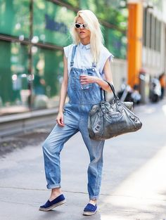 Blue denim overalls is worn over a blue button-up and paired with blue espadrilles and a black bag.