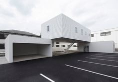Kunihiko Matsuba - Small white house over the flat rooftops of a dental clinic and garage near Tokyo