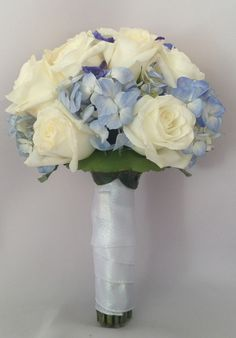 White and blue bridal wedding bouquet. Wedding. Roses, hydrangea and delphinium.