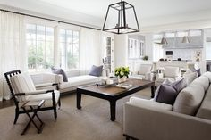 Transitional living room with iron and glass lantern over light gray linen sofa adorned with purple pillows paired with white armchairs, black chinoiserie coffee table, black spindle chair with vintage grain sack cushions as well as white bench situated in front of windows dressed in white curtains.