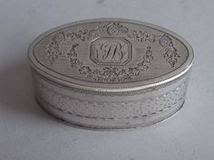 A very fine George III Pocket Nutmeg Grater. The Nutmeg Grater is oval in form and is engraved, on the cover, with Neo Classical floral garlands and roundels around a cut cornered cartouche, containing contemporary script initials. The sides are engraved with an eclectic mix of bright cut and prick dot bands and the base is beautifully engraved with prick dot sunburst designs around a central flower head, as well as floral bands.