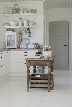 FARMHOUSE – INTERIOR – early american decor inside this vintage farmhouse seems perfect such as small simple rustic island, crisp white cabinets, open shelving, plank ceiling, gray door. Cottage Kitchens, Home Kitchens, Kitchen Dining, Kitchen Decor, Kitchen Grey, Kitchen Island, Kitchen Ideas, Island Table, Open Kitchen
