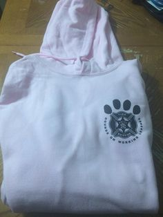 """Gildan Heavy Blend hooded sweatshirts in a light pink with black logo writing. Our logo is on the front with """"K-9 UNIT"""" on the back centered."""