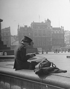 David E. Scherman, An Englishwoman in her Women's Auxiliary Air Force uniform reading a magazine with her gas mask beside her, London, September 1941.