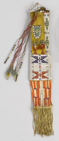 A Sioux beaded tobacco bag Beaded distinctly on each side, a small fringed pouch fastened on the yellow-dyed neck, trailing lengthy quill-wrapped thongs, beaded tabs and tin cones, the quilled slat section over fringe. length 31in