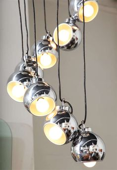 LUMI CHROME CHANDELIER    Exciting 9-light chandelier made in Milan by Lumi in the 1960's. Each shade has a magnet and can be adjusted to several positions. You can also adjust the wire to any length, unusual model.