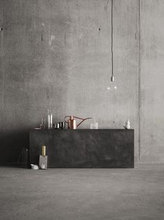 Grey concrete walls softened by glass and copper accessories by Coco Lapine Design #concrete #interiordesign #indigofurniture