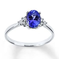 An oval tanzanite is the vibrant focal point of this lovely 10K white gold ring for her. Trios of round diamonds surround the center for contrast. Diamond Total Carat Weight may range from .085 - .11 carats.  Gently clean by rinsing in warm water and drying with a soft cloth.