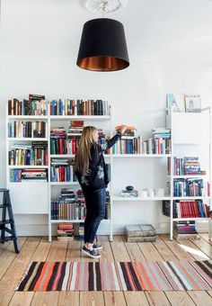 Copenhagen-based apartment with a small library featuring a large bookshelf with color coded books.