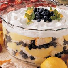 Blueberry Lemon Trifle  3 cups fresh blueberries, 2 cans (15¾ oz each) lemon pie filling or prepared vanilla or lemon pudding, 2 cups (8 oz) lemon yogurt, 1 prepared angel food cake, 8 oz frozen whipped topping, lemon slices & fresh mint for garnish