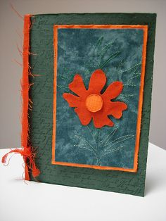 handcrafted card: Distressed Linen Flower ... not exactly a quilt but it has fabric and machine stitch lines for the flower leaves ... luv of the deep green and bright orange seem to dance in this color pairing ... top panel is fabric and so the the ribbon ... hybrid card ... like this card!! ... Hero Arts