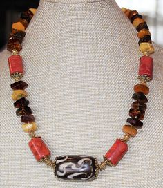 Thank you for visiting my Etsy Shop! Beautiful necklace and matching earrings with natural material with Tibetan gold plated beads and bead caps. The large center column bead is hand carved and dyed yak bone, with red sponge coral, and amazing Baltic amber in gorgeous shades of