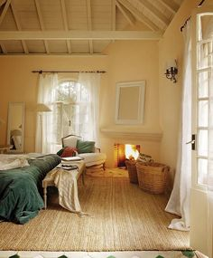 Bedroom with a fireplace and airy curtains - I'd add more colour to the room but it is beautiful
