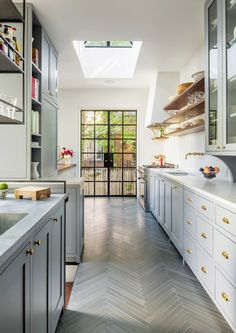 Narrow kitchen with skylight and herringbone tile floor